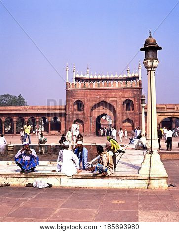 DELHI, INDIA - NOVEMBER 20, 1993 - Local men sitting around a pool at the Jama Masjid also known as the Friday mosque Delhi Delhi Union Territory India, November 20, 1993.