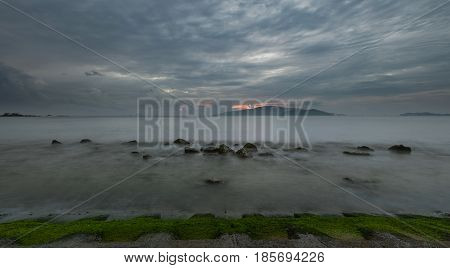 A moody morning slow exposure sky over Nha Trang bay Vietnam just before sunrise with moss foreground.