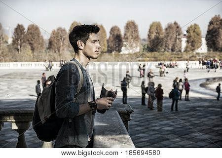 Half Body Shot of a Thoughtful Handsome Young Man, a Tourist, Holding a Guide, Looking Away Outside Historic Building in European City