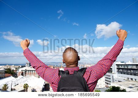 Back Of Man With Bag Raising Hands In The Air