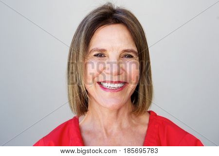 Close Up Smiling Older Woman Against Gray Background