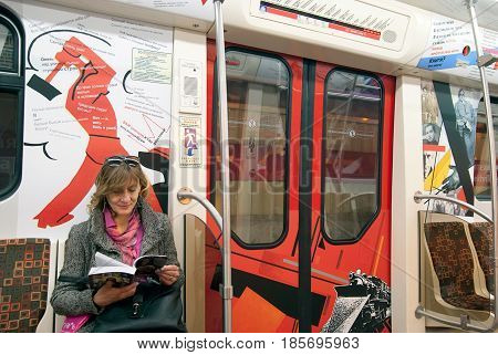 SAINT - PETERSBURG, RUSSIA - APRIL 28, 2017: Literary train. Unknown woman sitting and reading a book in the underground carriage with pictures and poems by Vladimir Mayakovsky