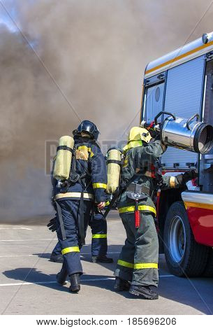 Team firefighters extinguish a fire in the smoke with the help of a fire engine