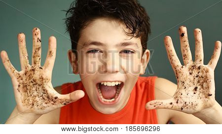 mischievous teen boy with dirty hand smiling close up portrait