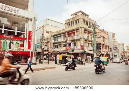BANGALORE, INDIA - FEB 14, 2017: Pedestrians and motorcycles moving past stores on busy indian street on February 14, 2017. With population 8.52 million Bangalore is 3-rd most populous indian city
