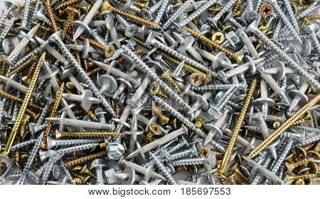 Many steel and brass screws and metal dowels scattered on flat surface