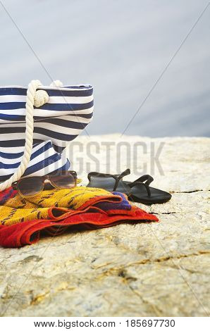Sunglasses towel bag and flip-flops on the beach. Summer holiday concept.