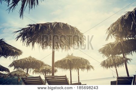 Straw Parasols at the tropical sandy beach. Retro filter.