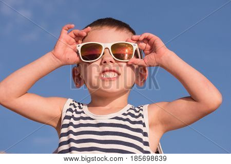 smiling little boy wearing white sunglasses with sea sunset reflection and sailor stripes vest showing teeth on blue sky background with copyspace