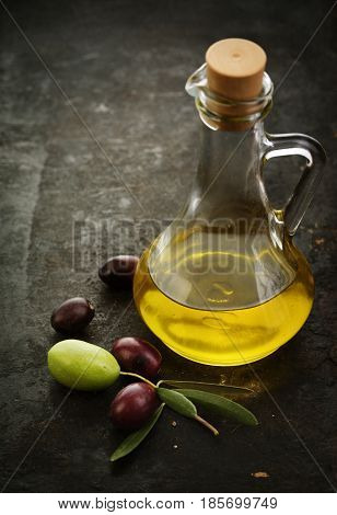 Olive oil and fresh oilves on black rustic background