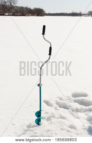 Fishing auger on an ice of the frozen river
