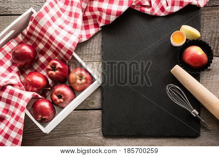Ripe red apples in birch-box on wooden board with red checkered napkin around and accessories for baking . Copy space on black slate dish.