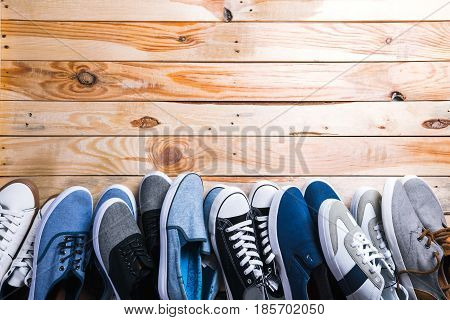 Various pairs of sneakers laid on the wooden floor background