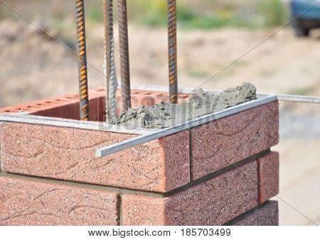 Installing Red Clinker Blocks and Caulking Brick Masonry Joints Exterior Wall.