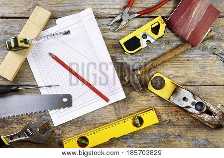 Various carpenter's tools on wooden table. Top view of craft workshop tools on rustic background.