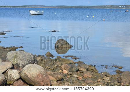 landscape in sweden with silent lake and boat reflections