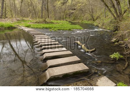 A concrete slab bridge crossing a river during spring.