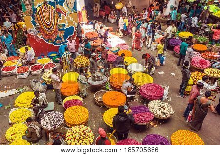 BANGALORE, INDIA - FEB 14, 2017: Customers and traders of huge Flower Market on busy indian street on February 14, 2017. With population 8.52 million Bangalore is 3rd most populous indian city
