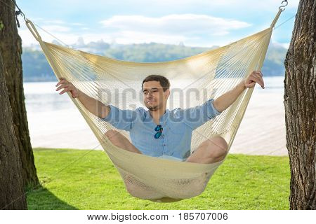 man relaxing in hammock in the park On a background of green grass and blue sky