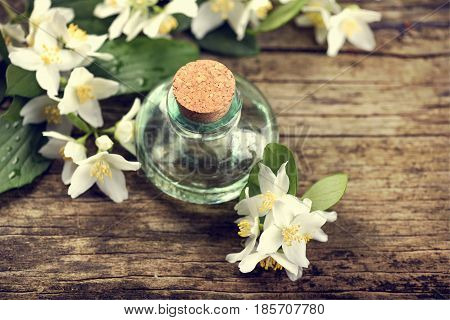 Essential oil with jasmine flower on rustic wooden table