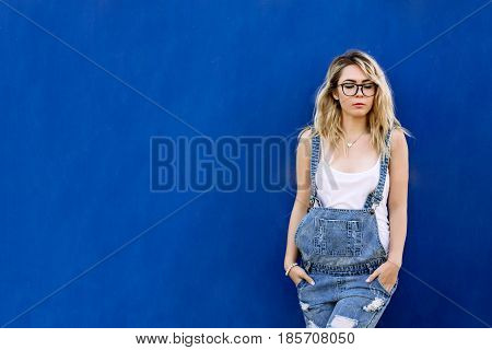 Young Stylish Blond Girl In Denim Overalls Made Of Denim And On A Blue Background