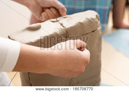 Extracurricular activities, ceramics. Clay for ceramics. Natural clay for ceramics Clipping the clay block with a vein.