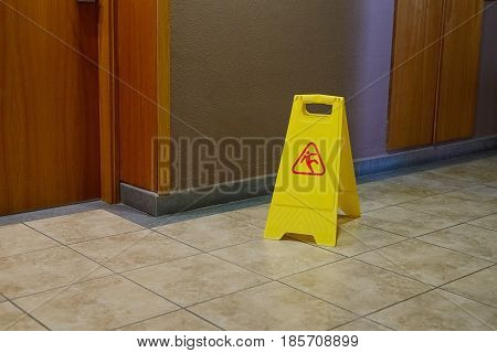 image of yellow label warning of slippery floor