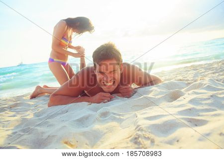 woman helping her boyfriend who stepped in a sea urchin