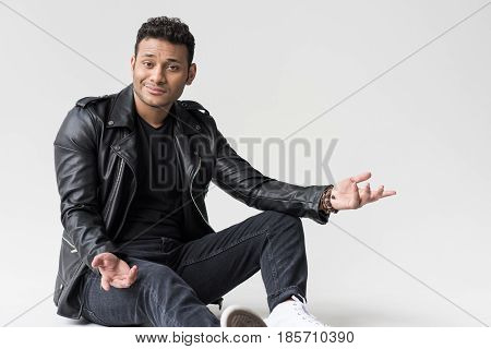 Young African American Man Sitting And Making Shrug Gesture Isolated On Grey