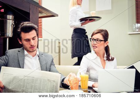 a young business couple is discussing important figures over their breakfast