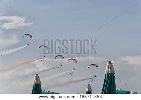 Bellaria Italy - June 05 2016: Paramotors with colored smoke trails in parade on the beach