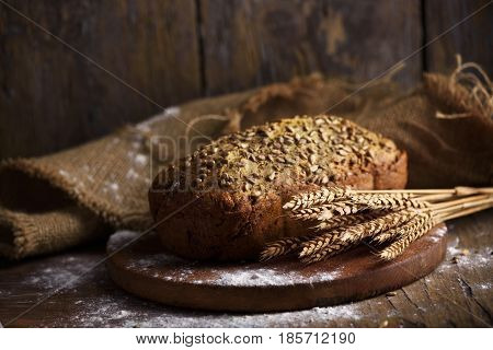 Homemade bread loaf and wheat ears on rustic wooden background