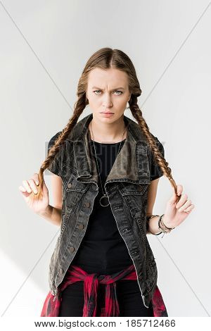 Portrait Of Attractive Blonde Rocker Girl With Braids Posing And Looking At Camera Isolated On Grey