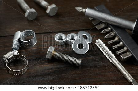 Mounting hardware made of metal. Screw bolts and clamp on a wooden background