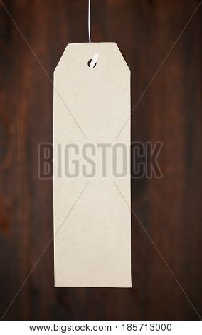 Paper tag on a woody background branded clothing label with information about discounts