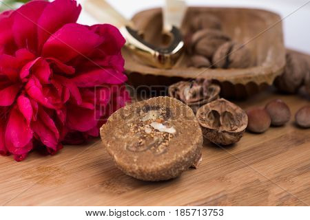 Walnuts, Hazelnuts, Cracked Nuts And Nutcracker In The Wooden Bowl On Brown Wooden Table With Red Fl