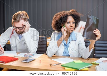 Multi ethnic group of medical students in uniform working on medical research sitting at the desk with x-ray and books in the modern classroom
