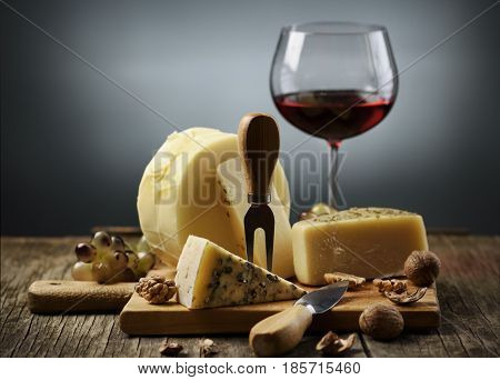 Cheese and red wine on wooden board.