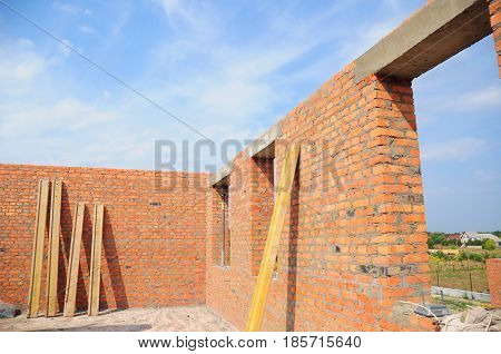 Unfinished house. House construction concept. Interior of a unfinished red brick house under construction. Closeup on windows hole construction with concrete lintel.