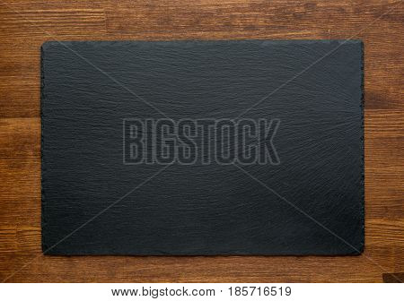 Black slate stone on wooden background, top view.