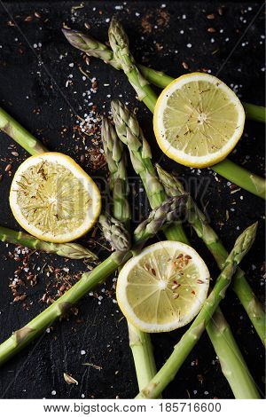 Asparagus with lemon and spices on black rustic plate