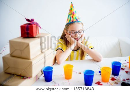 A teen girl is bored and sad on a birthday party