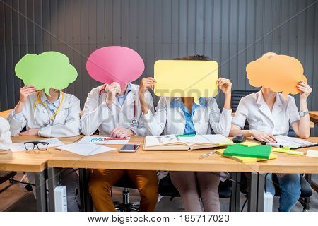 Portrait of multi ethnic group of medical students in uniform holding a colorful clouds sitting in a row at the desk in the modern classroom