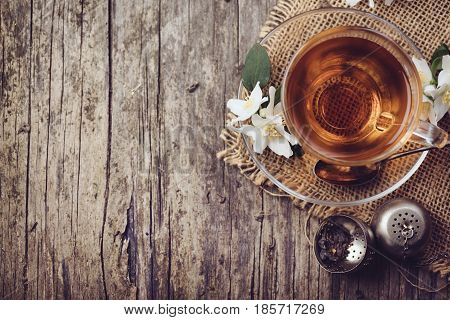 Cup of tea and jasmine flower on rustic wooden table Top view.