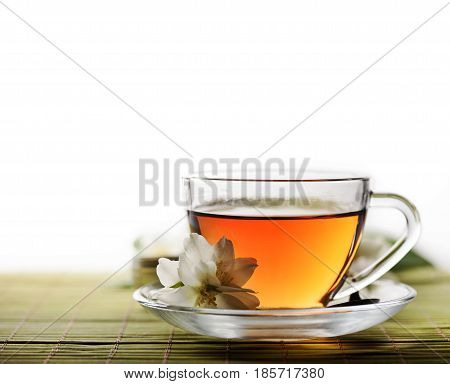 Tea cup with jasmine flowers and white copyspace