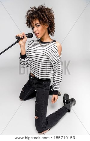 Beautiful Young Woman With Microphone Kneeling And Singing Isolated On Grey, Heavy Metal Singer Conc