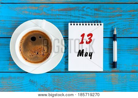 May 13th. Day 13 of month, calendar on white notepad with morning coffee cup at work place background. Spring time, Top view.