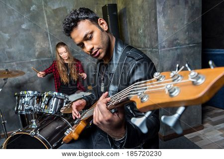 side view of man playing guitar with woman playing drums rock and roll band concept