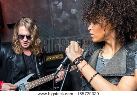 Side View Of Woman Singing In Microphone With Man Playing Guitar, Rock And Roll Girl Concept