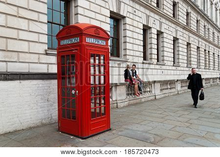 LONDON, UK - APRIL 13, 2007: Street scene with a traditional red telephone box a couple and a man talking to his phone on April 13, 2007 in London, UK.